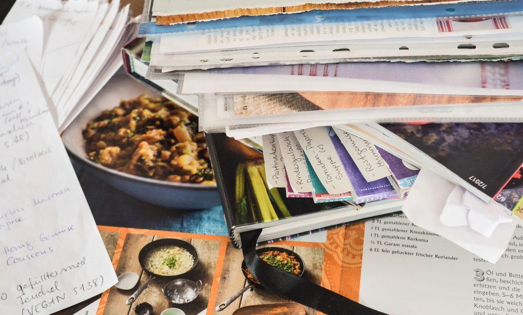 Speiseplan erstellen: Gestapelte Kochbücher und Rezepthefte mit Lesezeichen und Notizen