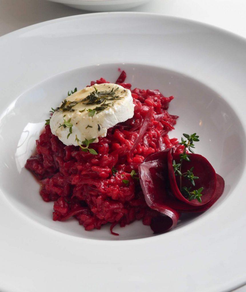 Rote-Bete-Risotto mit Ziegenkäse auf einem weißen Teller angerichtet