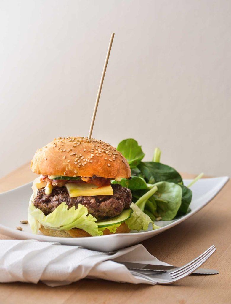 Klassischer Cheeseburger mit selbstgemachten Buns und Salat als Beilage